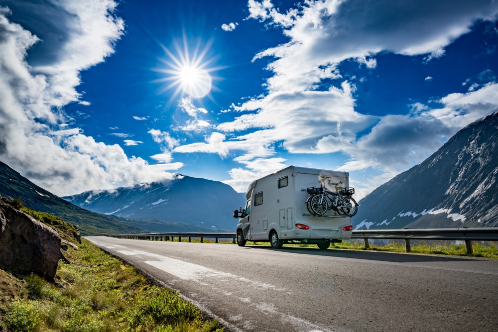 A white camper truck driving down a mountain road on a sunny day